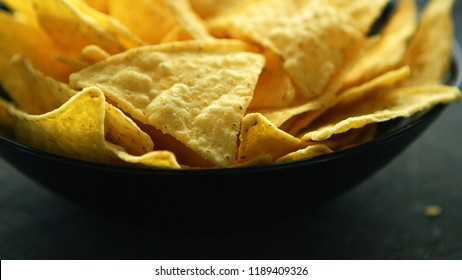 Closeup shot of bowl filled with crispy golden nacho chips and served on table in daylight