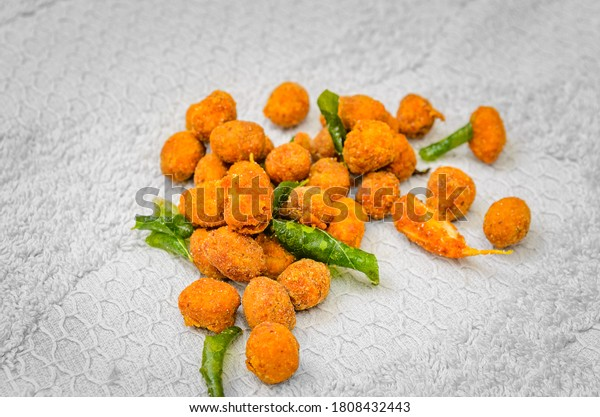Closeup Shot of a Bunch of Deep Fried Spicy Masala Peanuts along with Fried Curry Leaves and Garlic on a white cloth