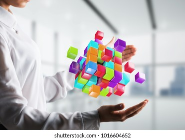 Closeup shot of business woman hands holding multiple cubes of different colours in hands with office view background. Mixed media.