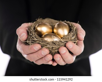 Close-up shot of a businessman holding nest in hands with golden eggs.