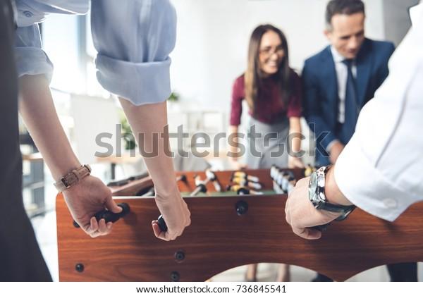 Nahaufnahme von Geschäftsleuten, die im modernen Büro Tischfußball spielen