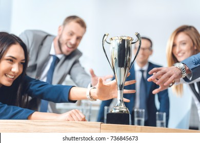 close-up shot of businesspeople trying to catch champion cup - Shutterstock ID 736845673