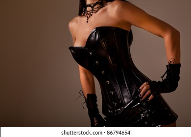 Close-up shot of busty woman in black leather corset, studio shot on golden background
