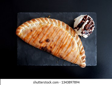 close-up shot of calzone with nutella and whipped cream on black slate