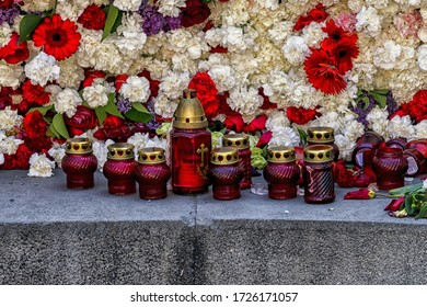A closeup shot of candle jars and flowers on a memorial monument