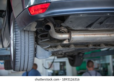 A closeup shot of a car parked in an automobile repair shop for an inspection