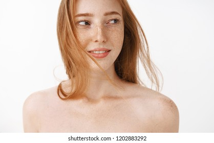 Close-up shot of charming sensual and feminine redhead female with freckles posing naked being tender and gentle turning right glancing flirty and delighted standing over white background