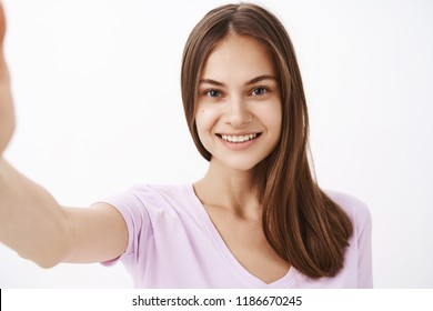 Close-up shot of charming young happy european female brunette with long strong hair and clean sking smiling friendly at camera while pulling hand forward as if taking selfie over white background
