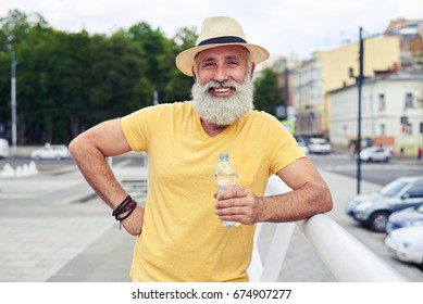 Close-up shot of cheerful bearded man holding bottle of water against cityscape
