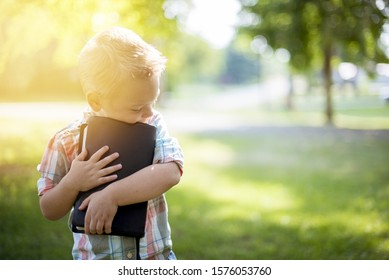 A closeup shot of a child holding the bible against his chest with a blurred background