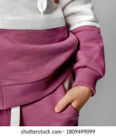 Close-up shot with a child's hand in a sweatpants pocket. Fragment of a photograph of a child in a sports sweatshirt and trousers, isolated on a gray background. Advertising of fashionable sportswear