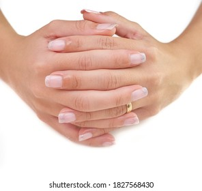 A closeup shot of clasped female hands with a wedding ring