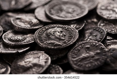Close-up shot of coin of roman emperor Maximinus among other coins, selective focusing