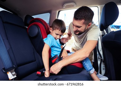 Close-up shot of concentrated father helping his son to fasten belt on car seat