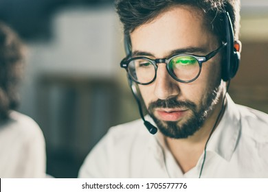 Closeup shot of confident bearded call center operator. Handsome bearded young man sitting at workplace. Call center concept