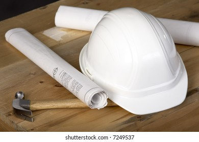 Closeup shot of a construction hardhat and blueprints