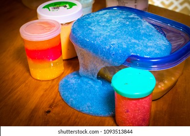 A closeup shot of containers holding different colored slime toys with a blue slime toy cascading over its container like a waterfall.  Slime is a very popular toy amount children.