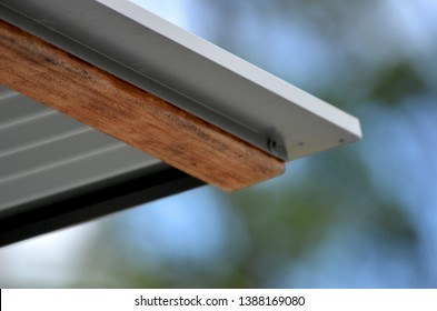 A close-up shot of the corner of a corrugated iron roof with a gutter. A wooden beam supports the roof. The background is out of focus.