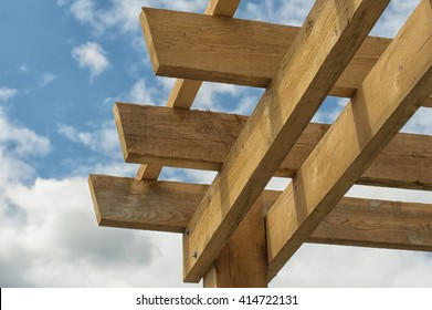 Closeup shot at the corner of a wooden pergola against blue sky background