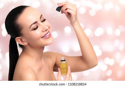 Closeup shot of cosmetic oil applying on young woman's face with pipette. Beauty therapy concept. Abstract background with blurred lights