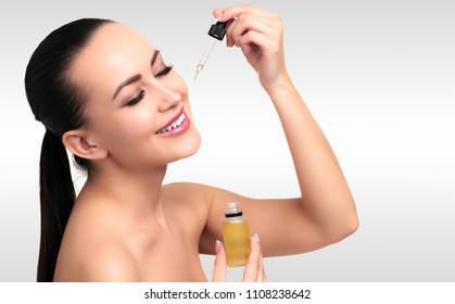 Closeup shot of cosmetic oil applying on young woman's face with pipette. Beauty therapy concept. Grey steel background