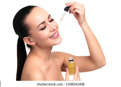 Closeup shot of cosmetic oil applying on young woman's face with pipette. Beauty therapy concept. Isolated on white background