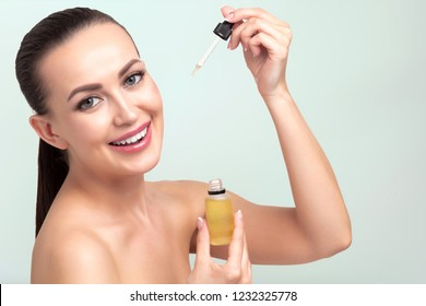 Closeup shot of cosmetic oil applying on young woman's face with pipette. Beauty therapy concept.