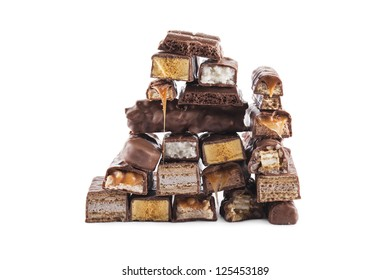 Close-up shot to the creamy chocolate bars with nuts arranged in a pyramid shape on a white background