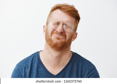 Close-up shot of cute and funny adult with red hair and beard, crying and being gloomy, closing eyes, frowning, tilting head back while pursing lips, feeling regret or upset over gray background