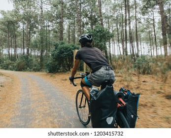 closeup shot of cyclist speeding up on the road through forest trees