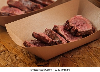 Closeup shot of delicious beef slices in craft paper container on street food festival