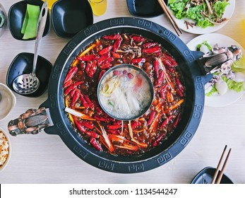 Closeup Shot of The Delicious Chinese Food, Super Hot and Spicy Sichuan Hotpot Showing Chillis, Sichuan Pepper Seeds and Other Chinese Herbs in The Oil Soup.