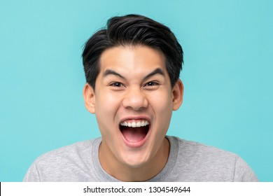 Closeup shot of delighted excited Asian man face isolated on light blue background