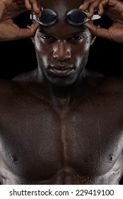 Close-up shot of determined male swimmer with goggles looking at camera. Young african man with wet body.