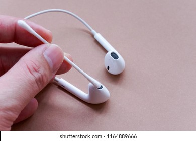 Closeup Shot of Earphones Cleaning by Using Cotton Bud on Brown Background