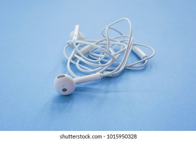 Closeup Shot of Earphones or Smalltalk with Tangled Cable on Blue Background