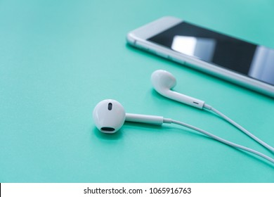 Closeup Shot of Earphones with Smartphone on Turquoise Background