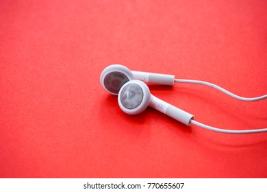 Closeup Shot of Earphones for Smartphone on Red Background