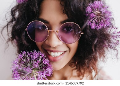 Close-up shot of ecstatic african woman laughing during photoshoot with allium. Studio portrait of curly black girl expressing happiness.