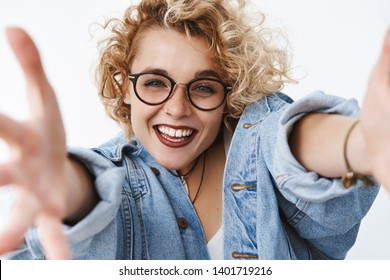 Close-up shot of enthusiastic and charismatic funny joyful stylish woman with short curly hair extending hands towards camera to hold product or give warm hug, wanting cuddle feeling joyful