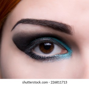 Close-up shot of an eye with artistic blue and black makeup