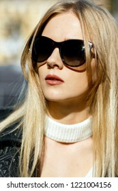 Closeup shot of fabulous blonde woman with long hair wearing leather jacket and sunglasses