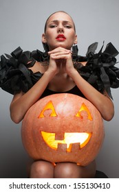 Closeup shot of fashionable model in exclusive black dress sitting with pumpkin