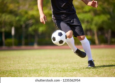 close-up shot of feet of asian soccer player handling the ball on football field.