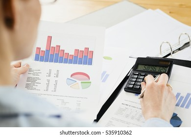 Closeup shot of a female accountant reading a financial report. Shallow DOF, focus on the paperwork and calculator.