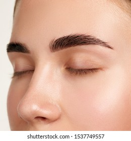 Closeup shot of female closed eye and brows with day makeup amazing brow
