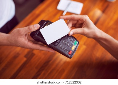 Closeup shot of female hand paying with card with wooden counter in background