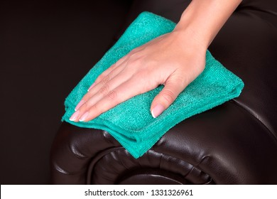 Closeup shot of female hand wiping brown leather chester couch or sofa