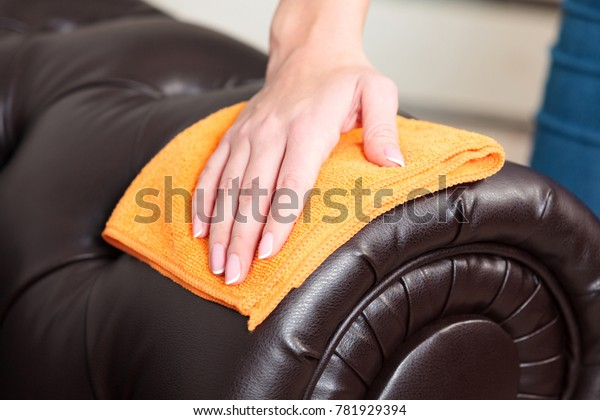 Closeup shot of female hand wiping brown leather chester couch of sofa