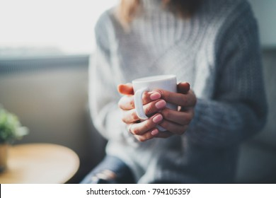 Closeup shot of female hands holding cup of hot tea or coffee